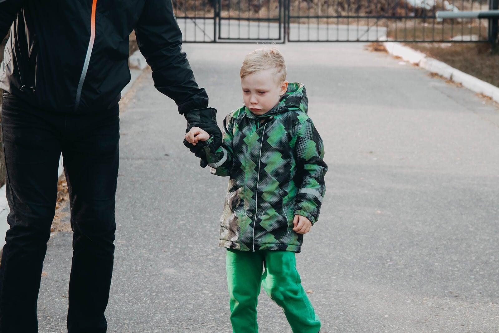 Niño llorando triste de la mano de su padre.