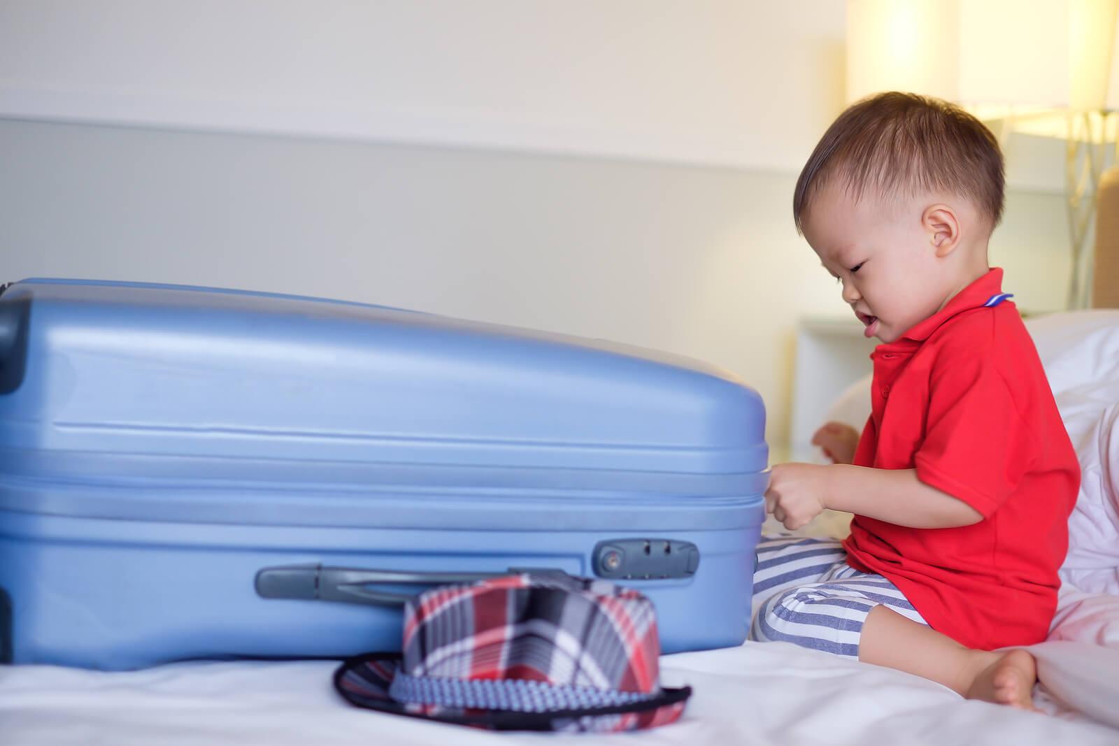 Niño preparando la maleta para salir de viaje.
