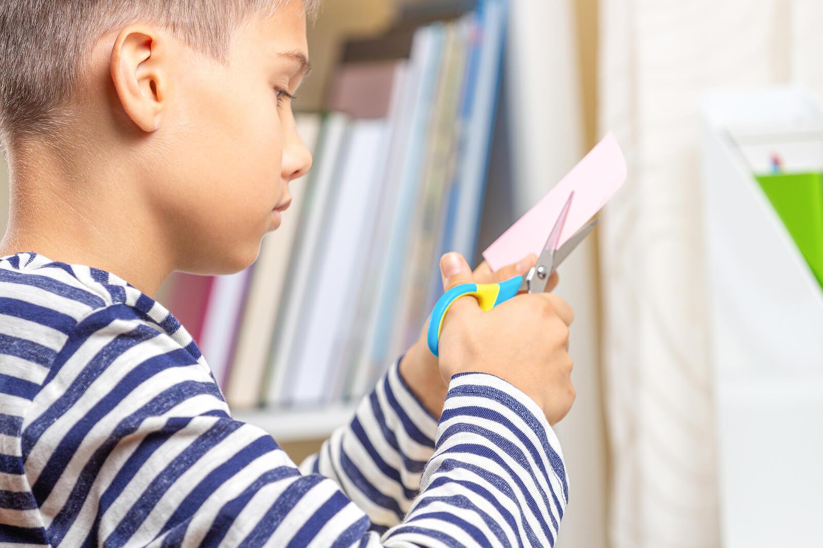 Un enfant qui découpe du papier.