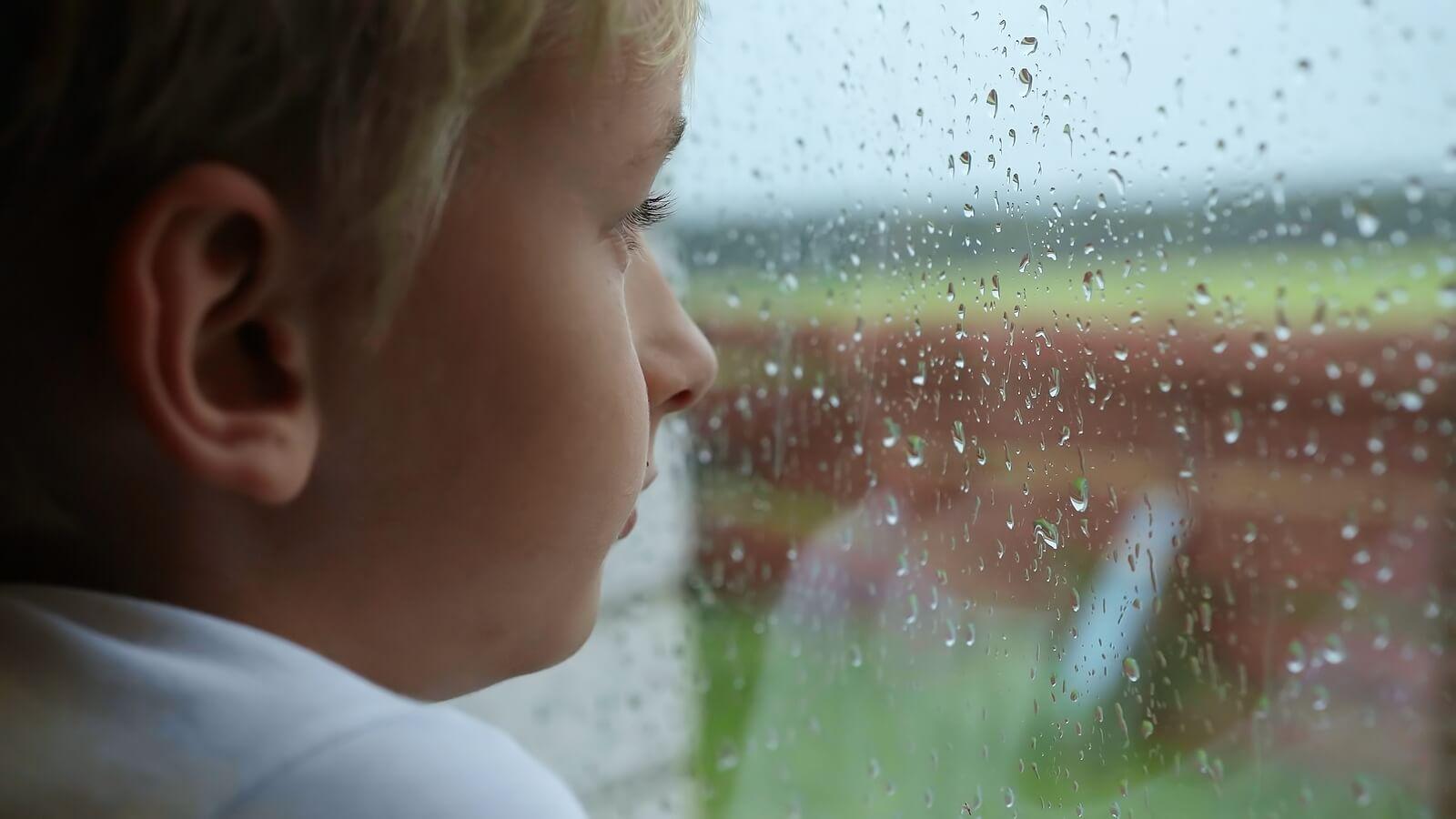 Niño mirando por la ventana pensado en el suicidio.