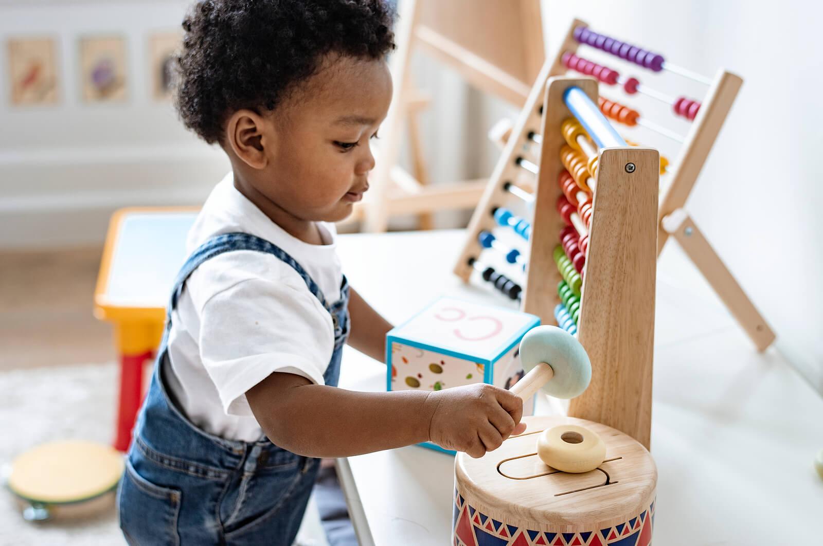 Niño jugando con juguetes Montessori.