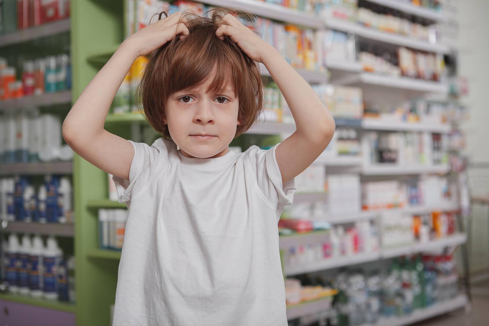 Niño con picor en la cabeza porque sufre pediculosis.