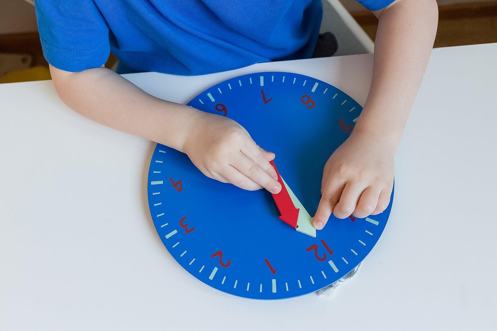 Niño aprendiendo matemáticas con un reloj gracias al método Montessori.