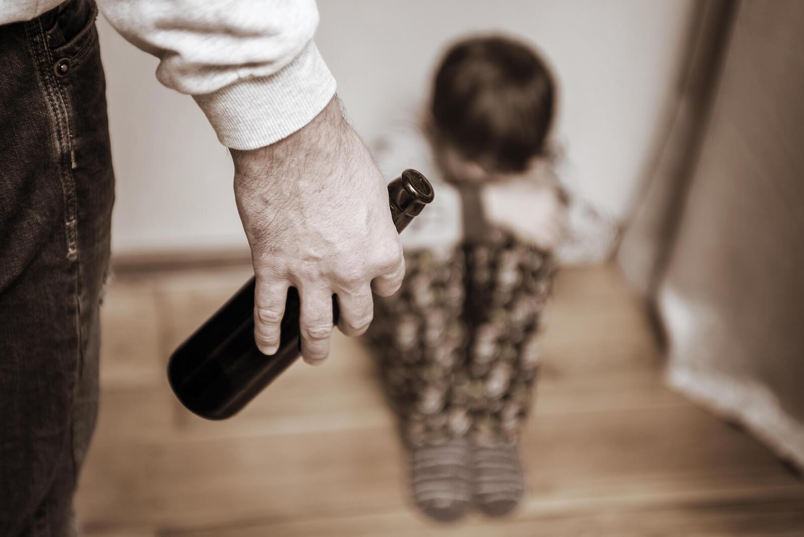 Hijo de padre alcohólico asustado en el suelo.