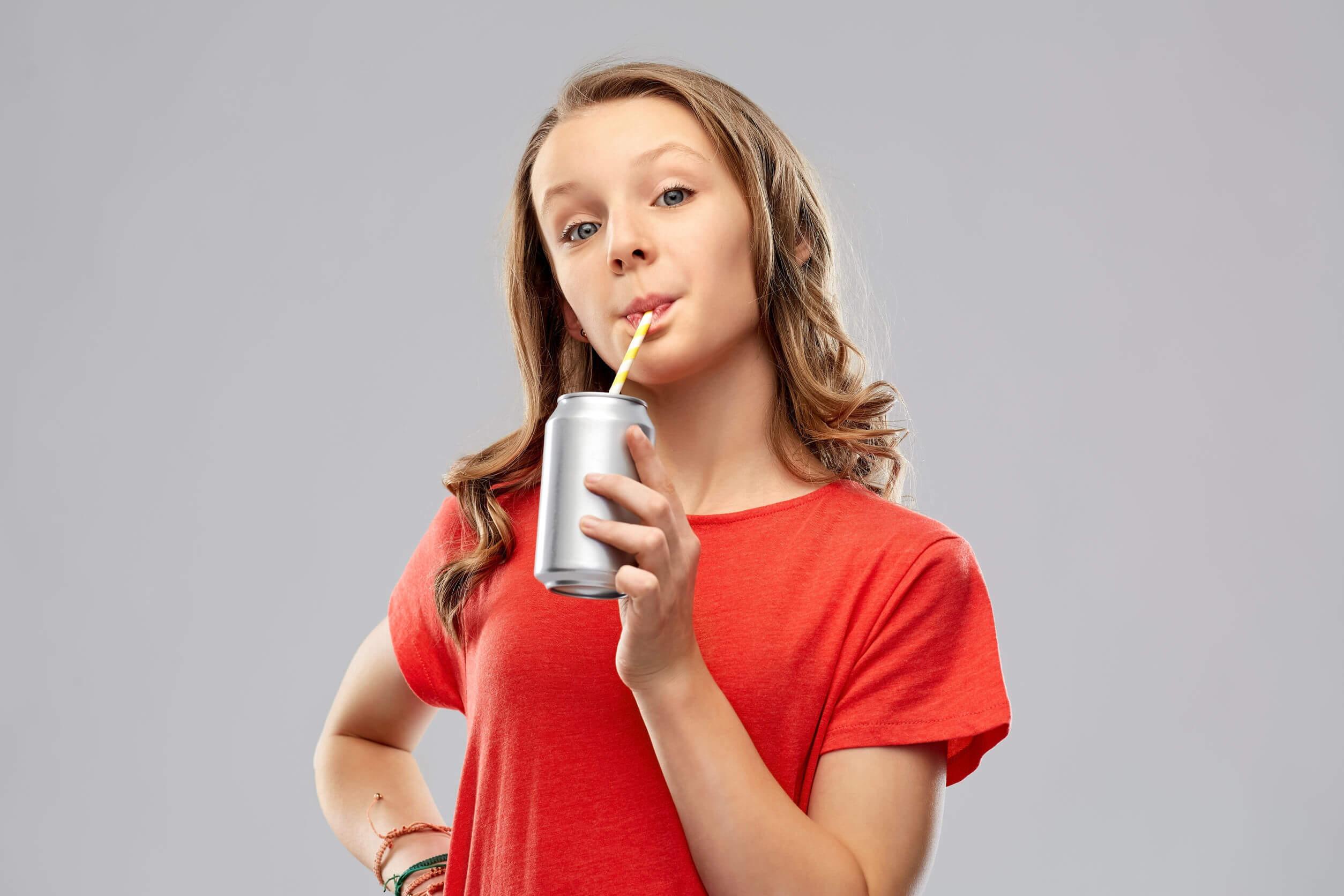 Chica adolescente bebiendo un refresco con muchos carbohidratos y azúcar.