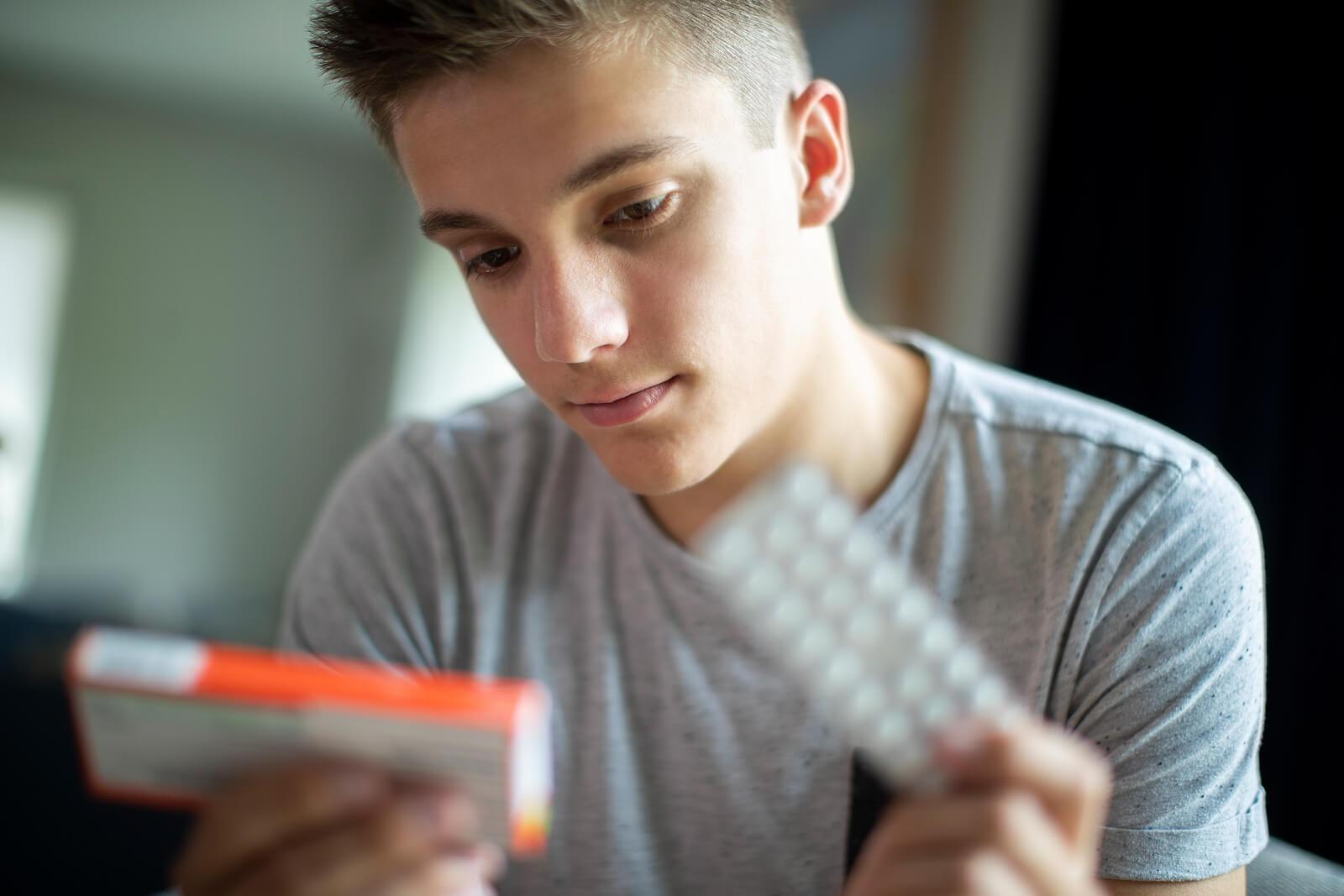 Chico mirando unas pastillas con pensamientos suicidas.