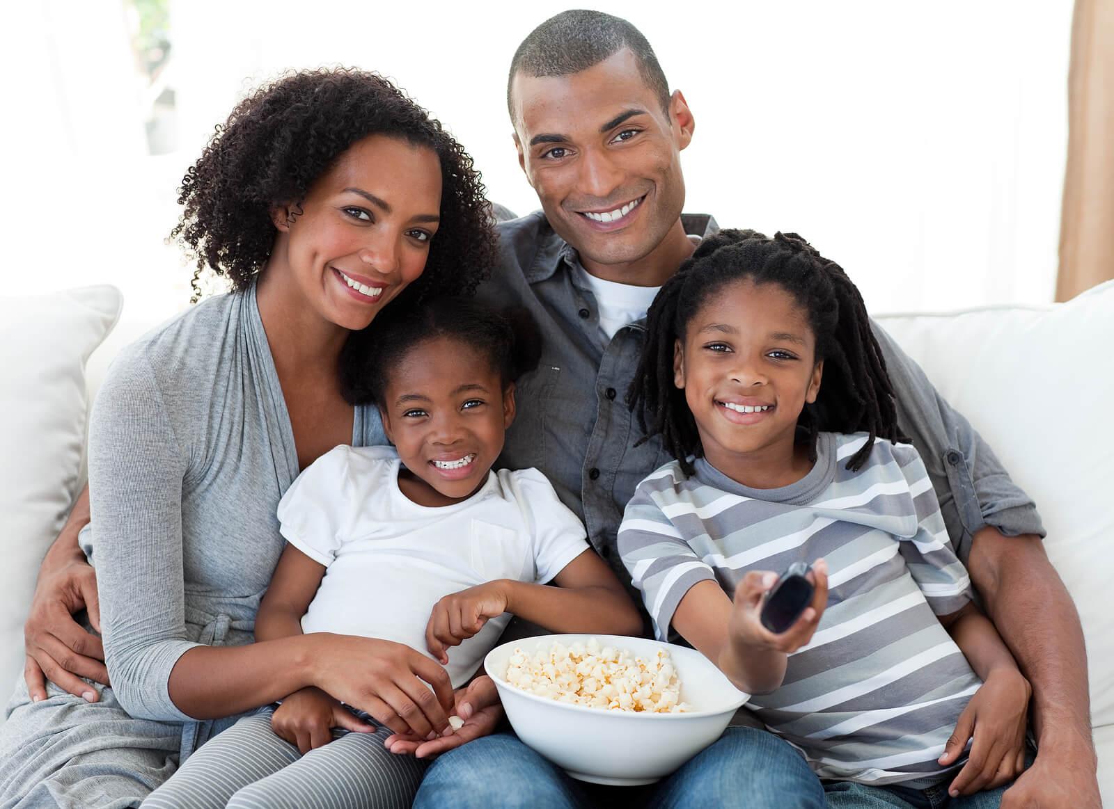 Padres con sus hijos viendo una película.