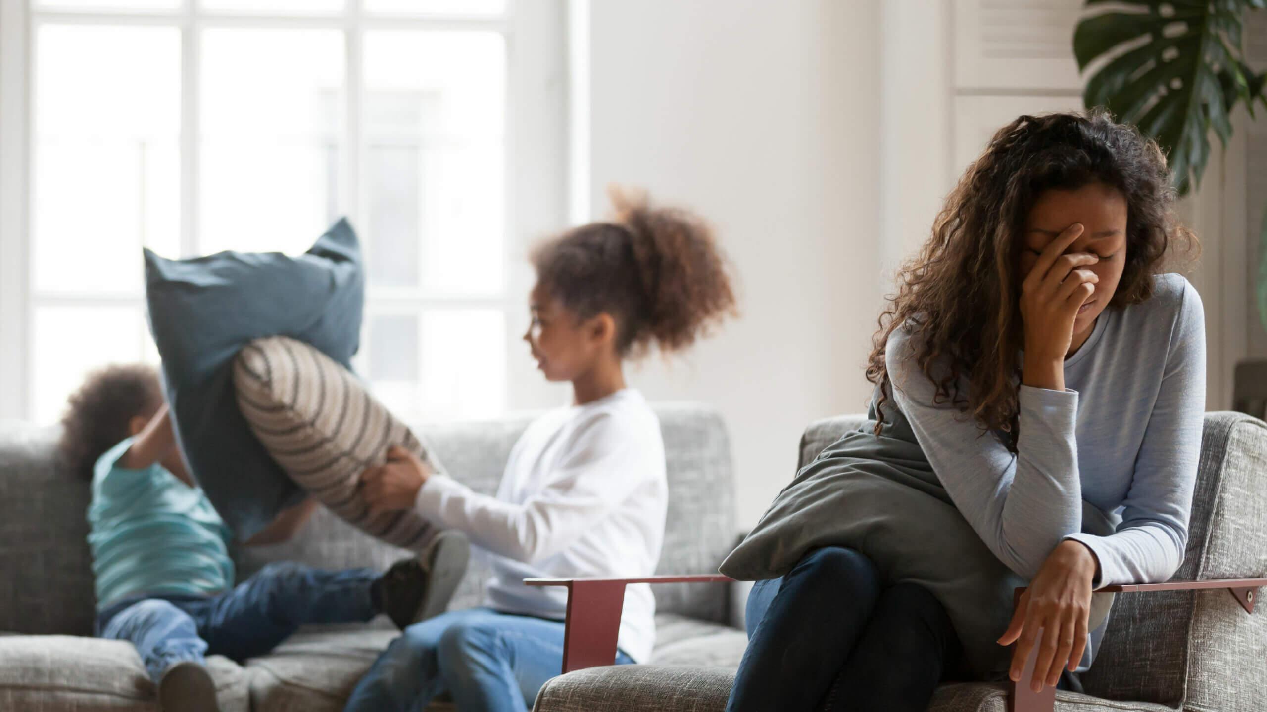 Madre agotada de las peleas de sus hijos padeciendo el síndrome de burnout parental.