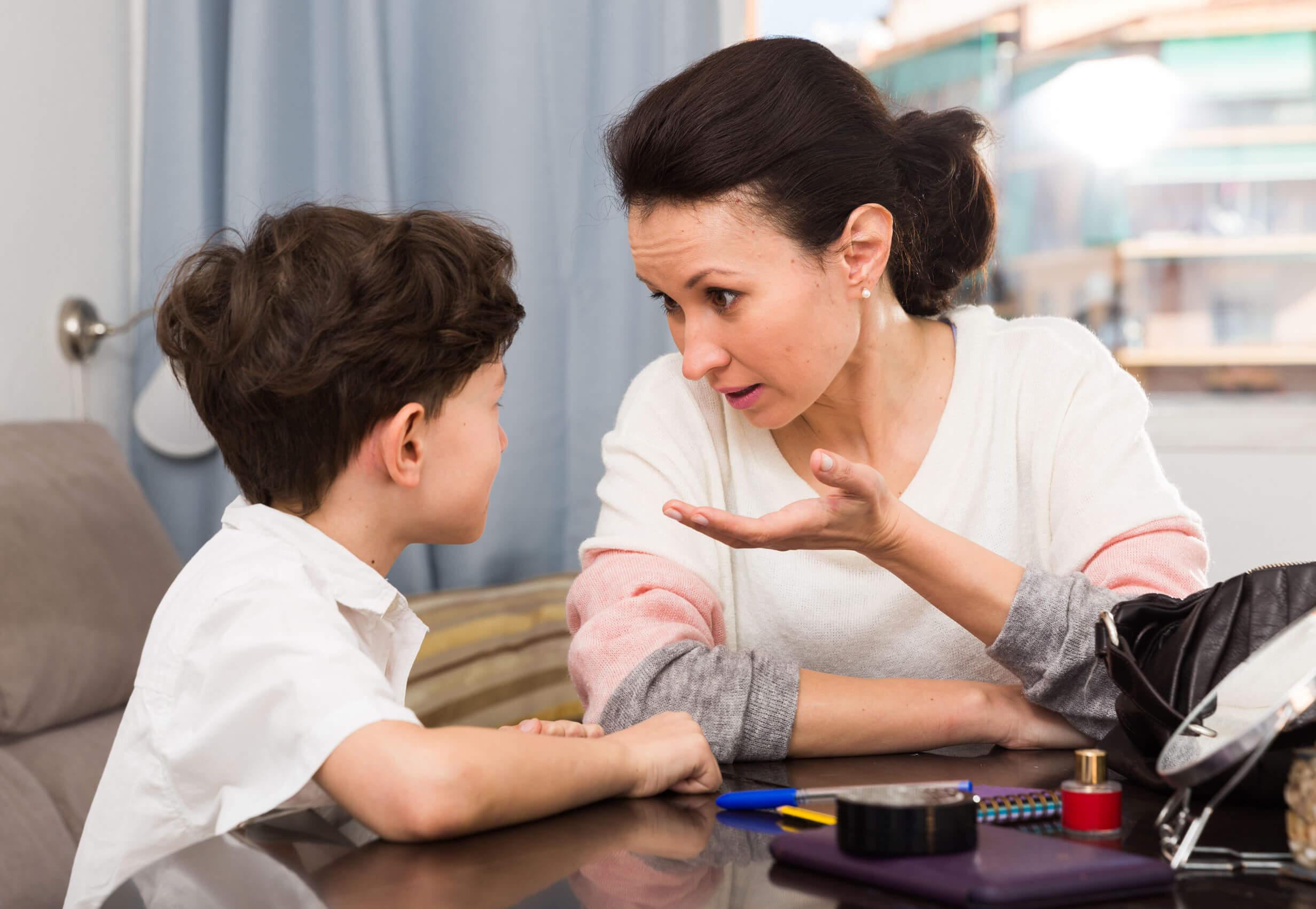 Madre hablando con su hijo para enseñarle cuando tiene que parar de hablar.