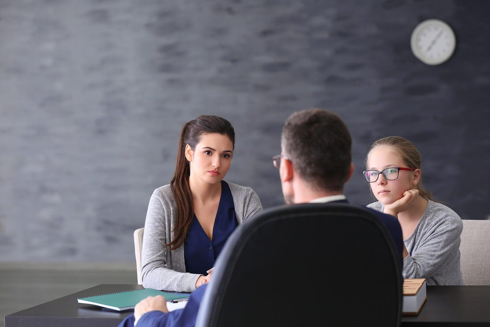 Madre con su hija en una reunión con su profesor para mantener una relación fluida.