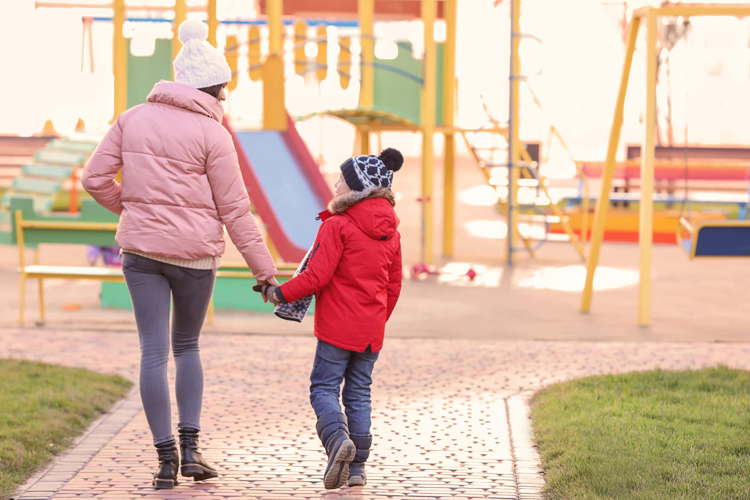 Madre dando un paseo por el parque con su hijo adoptado.