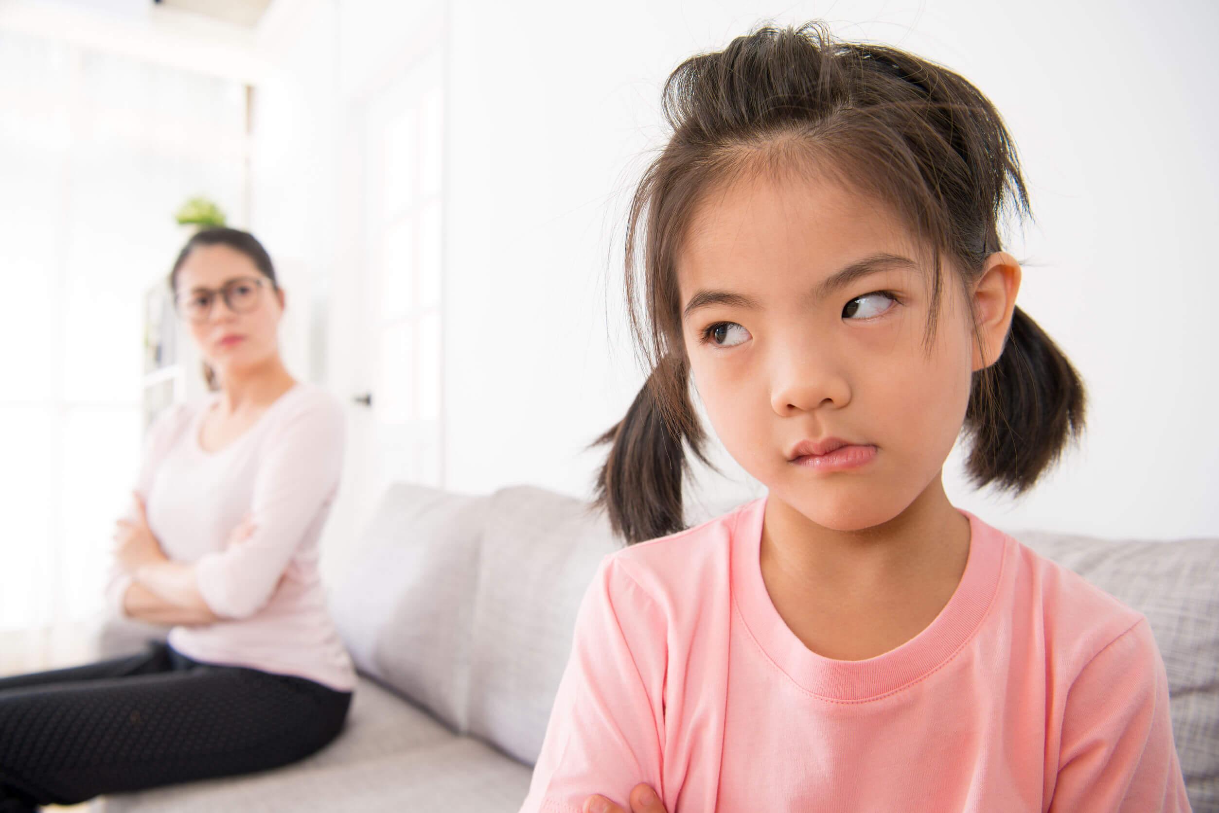 Niña muy enfadada con su madre, a la que no quiere dar un abrazo.