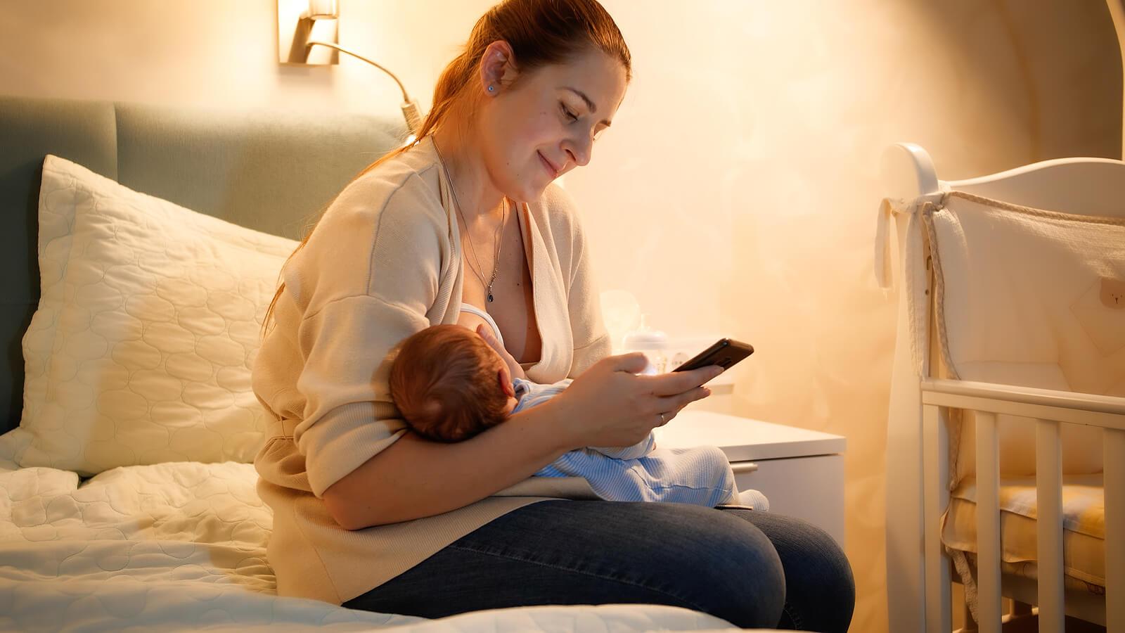 Mamá dándole el pecho a su bebé mientras consulta algunas de las apps para que la ayudarán a cuidarlo.