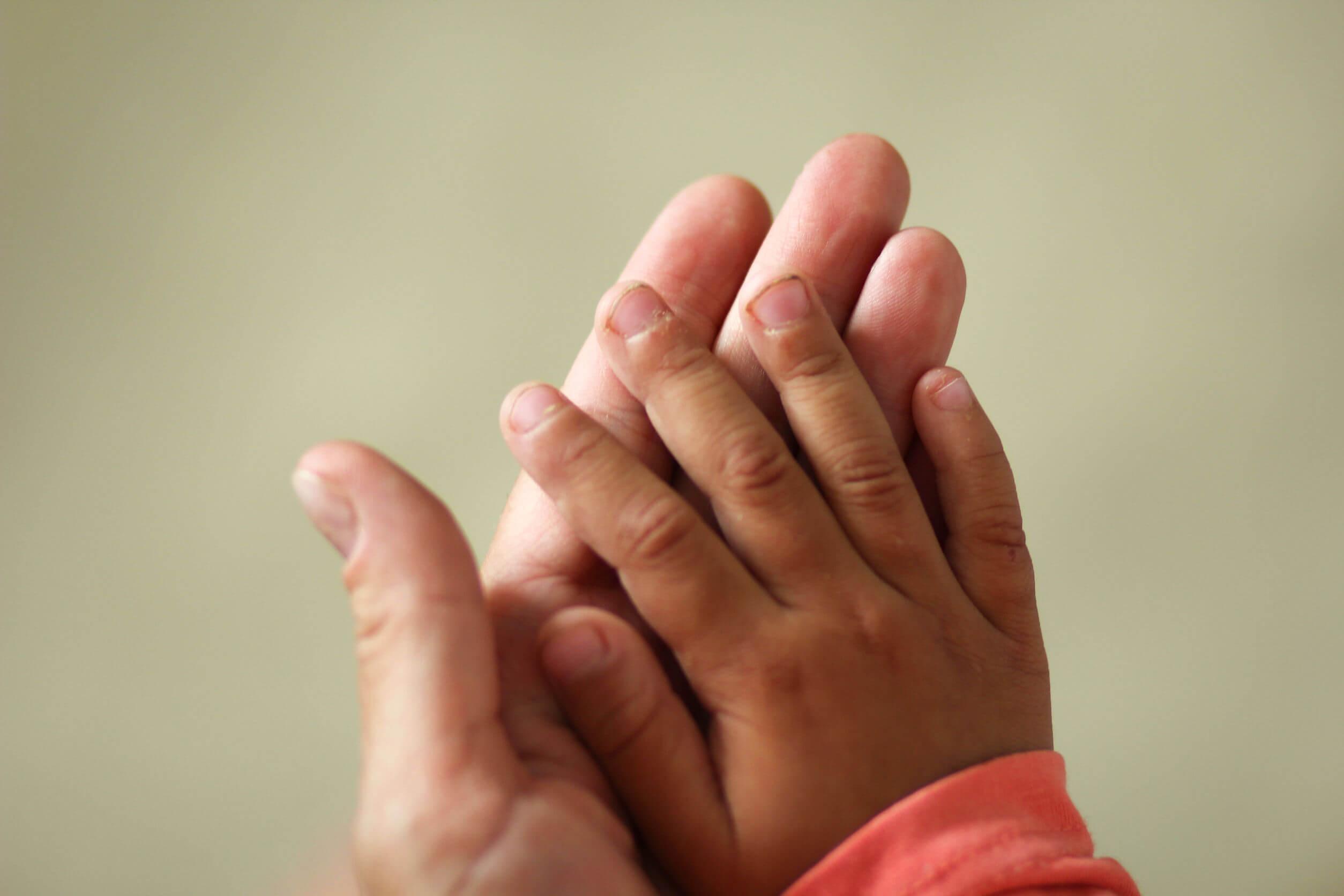 Manos de un niño con las uñas sucias.