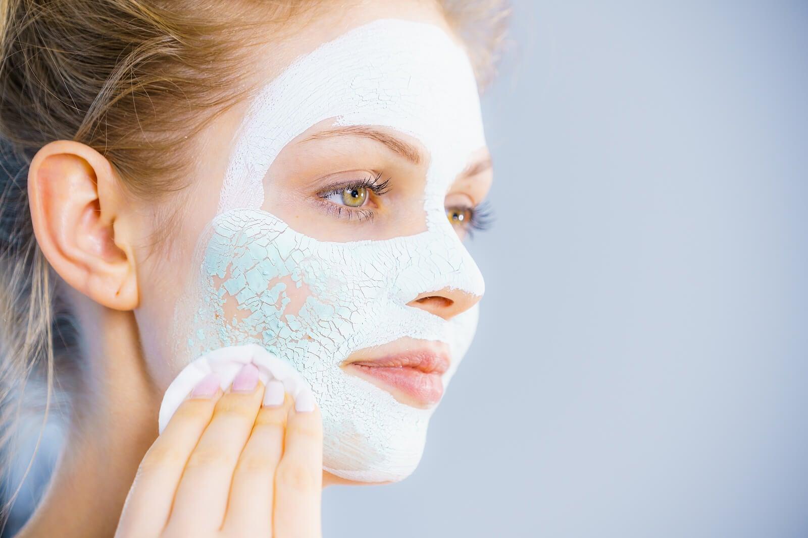 Mujer con la piel grasa aplicando una mascarilla de arcilla.