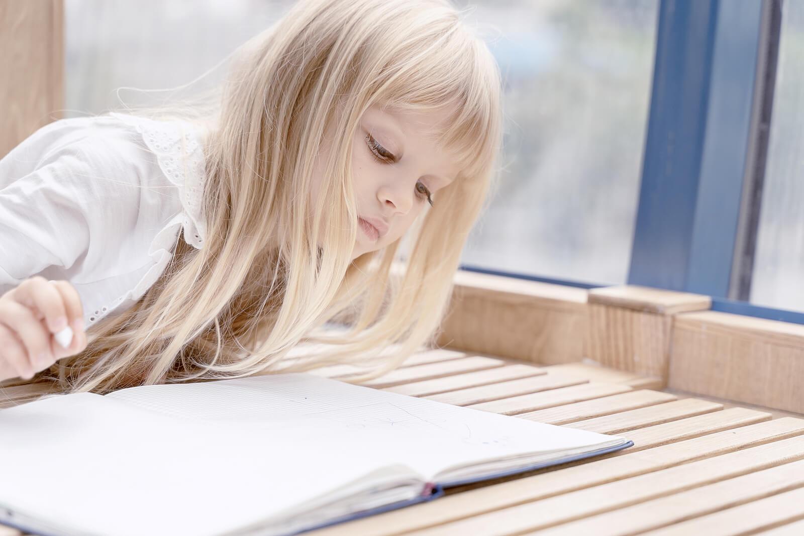 Niña pensando en la escritura a mano mientras observa un cuaderno.