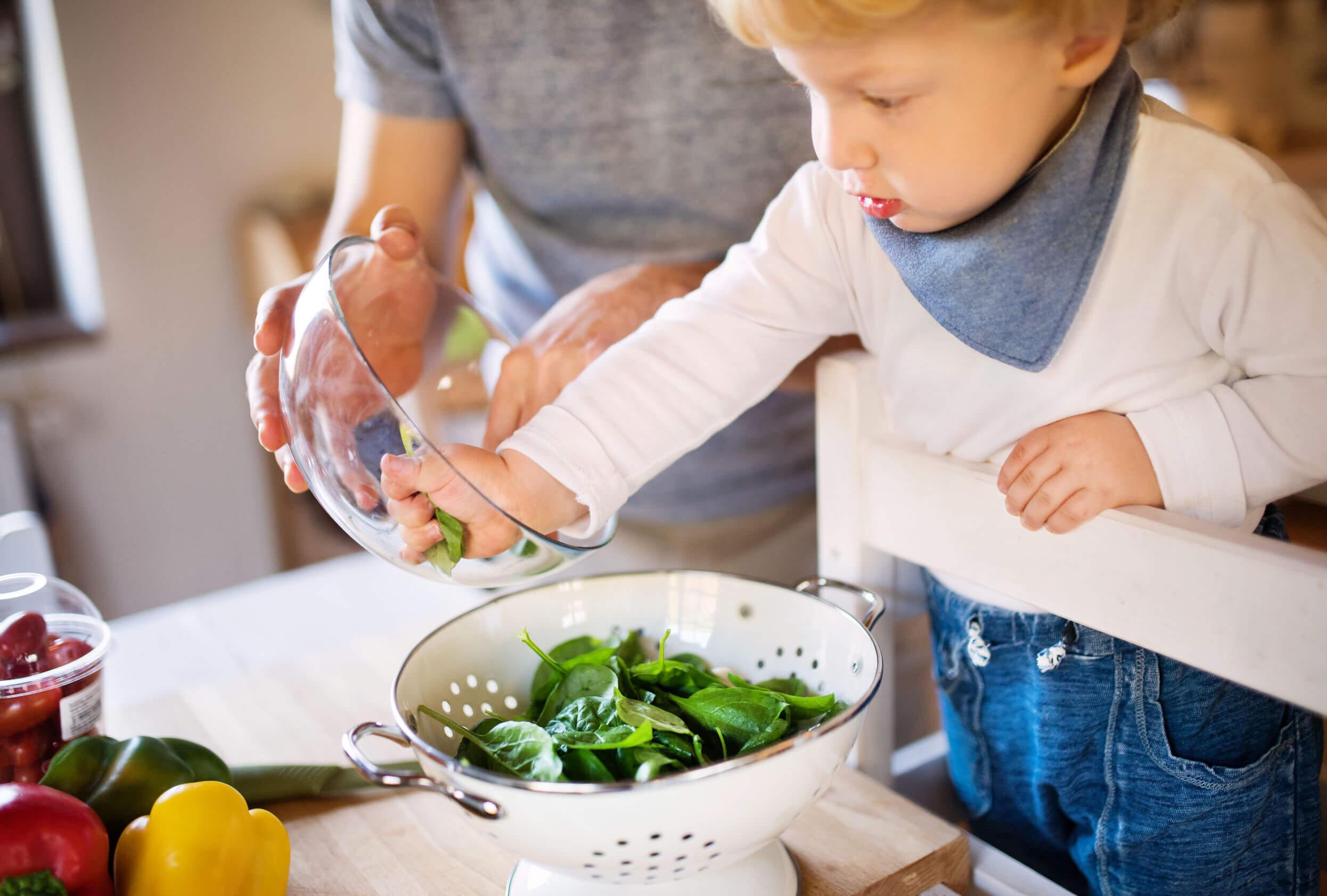Niño ayudando a su padre en la cocina debido a los beneficios infantiles que tienen cocinar con los padres.