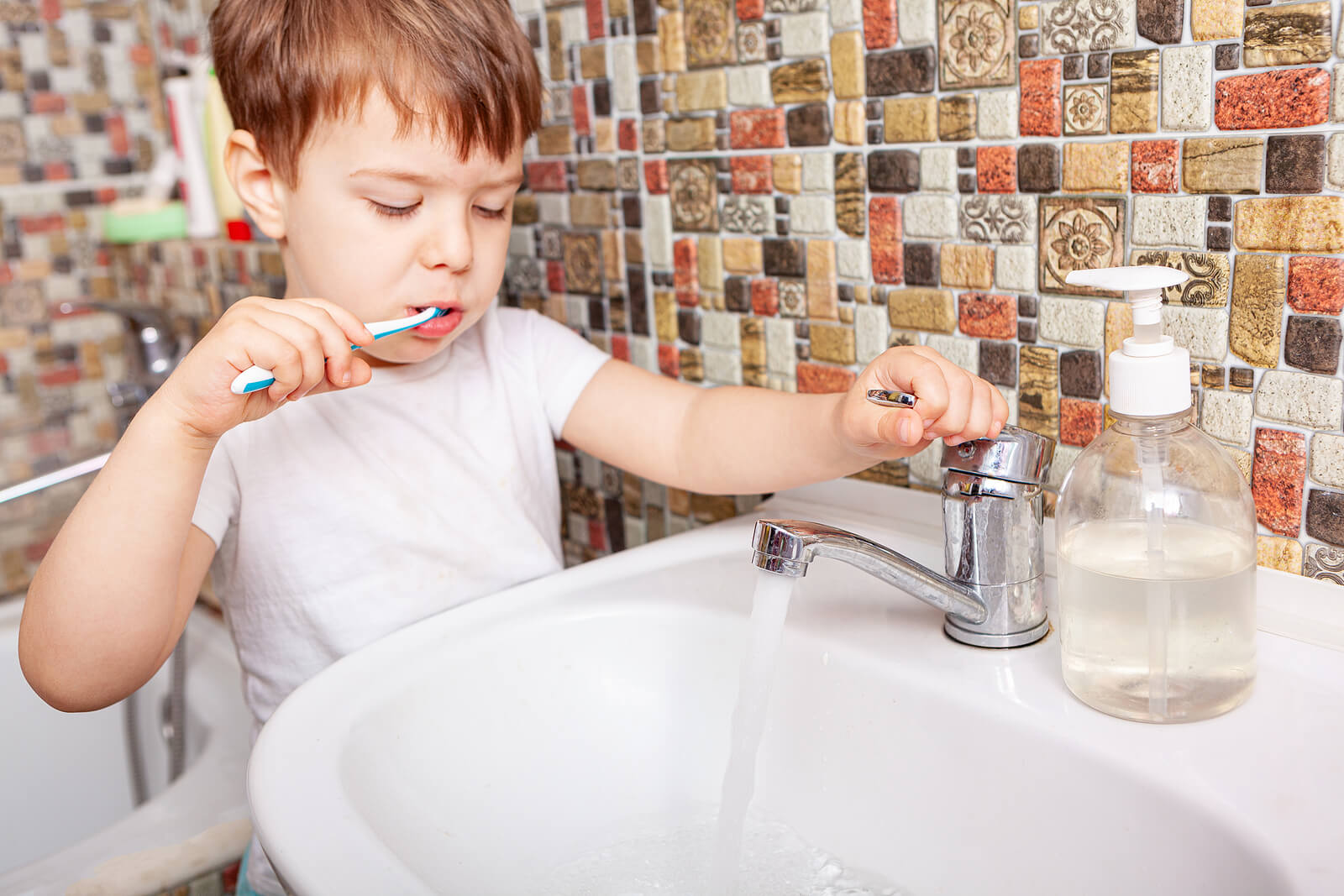 Niño cepillándose los dientes para no tener sarro.