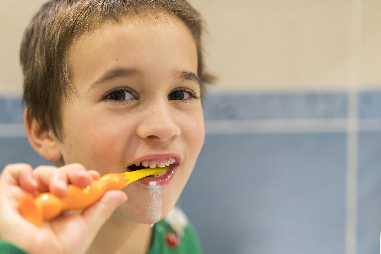 Niño lavándose los dientes con una pasta con flúor.