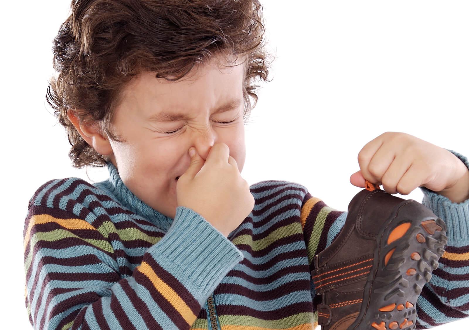 Niño con la nariz tapada debido a que sus zapatos huelen muy mal.