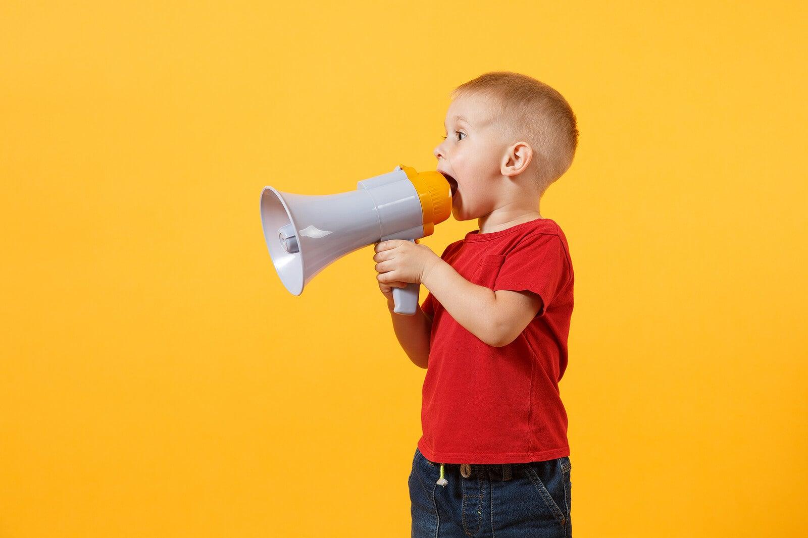 Niño hablando con un megáfono para el desarrollo el lenguaje entre 1-2 años.