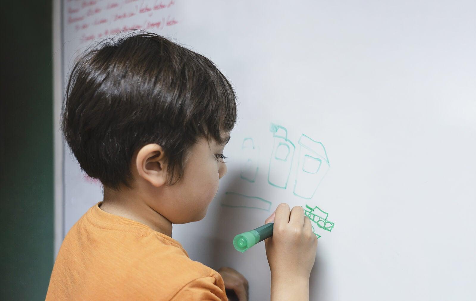 Niño escribiendo en una pizarra en casa.