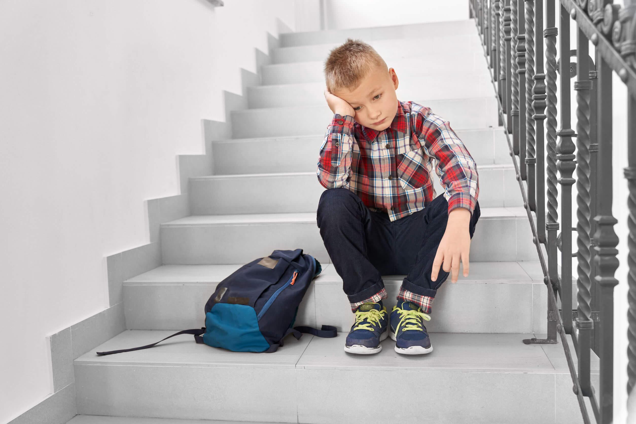 Niño sentado en las escalera del colegio con miedo al fracaso.