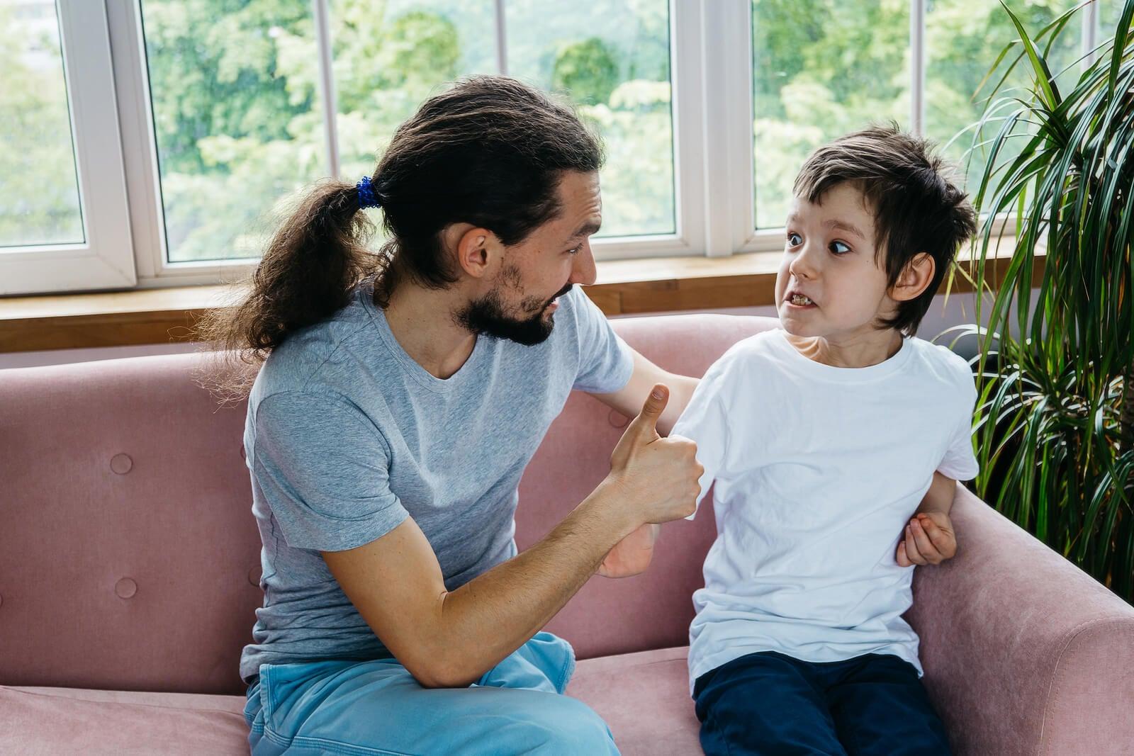 Niño con trastornos de tics hablando con su padre.