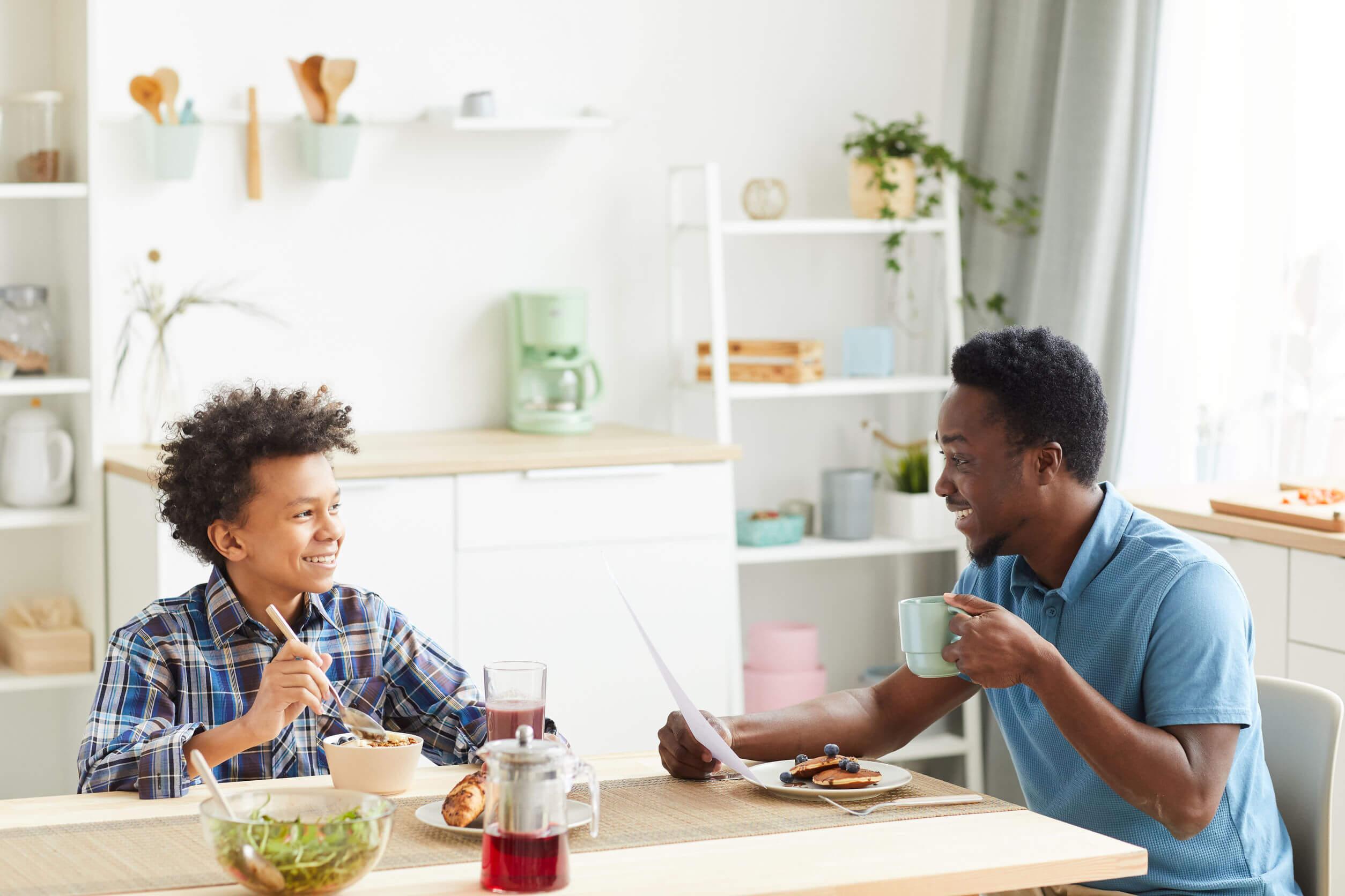 Padre hablando con su hijo mientras comen para mejorar la confianza de los jóvenes.