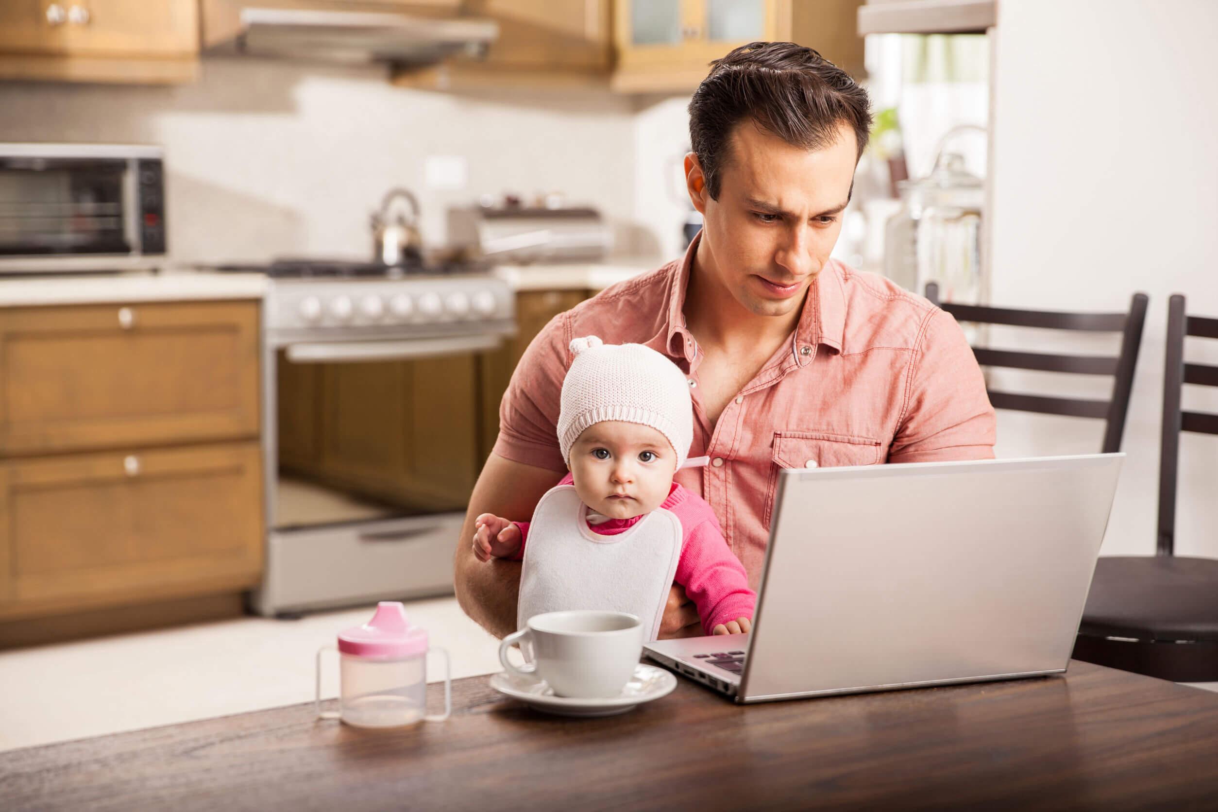Padre cuidando a su hijo mientras teletrabaja, uno de los retos actuales de la paternidad.