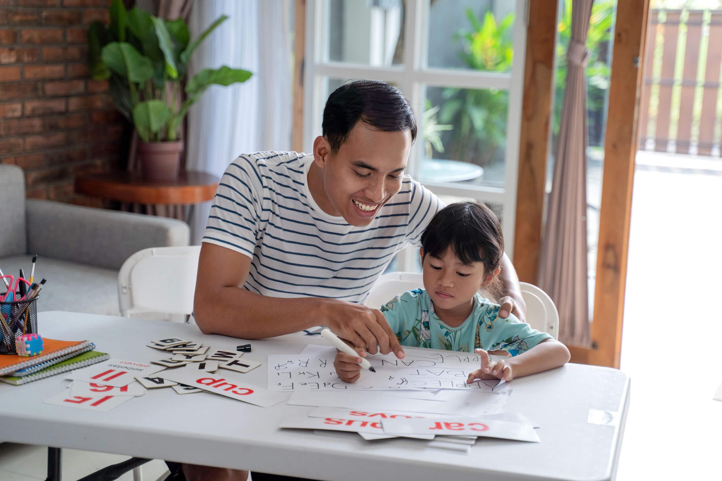 Padre ayudando a su hija a estudiar para darle una buena educación.