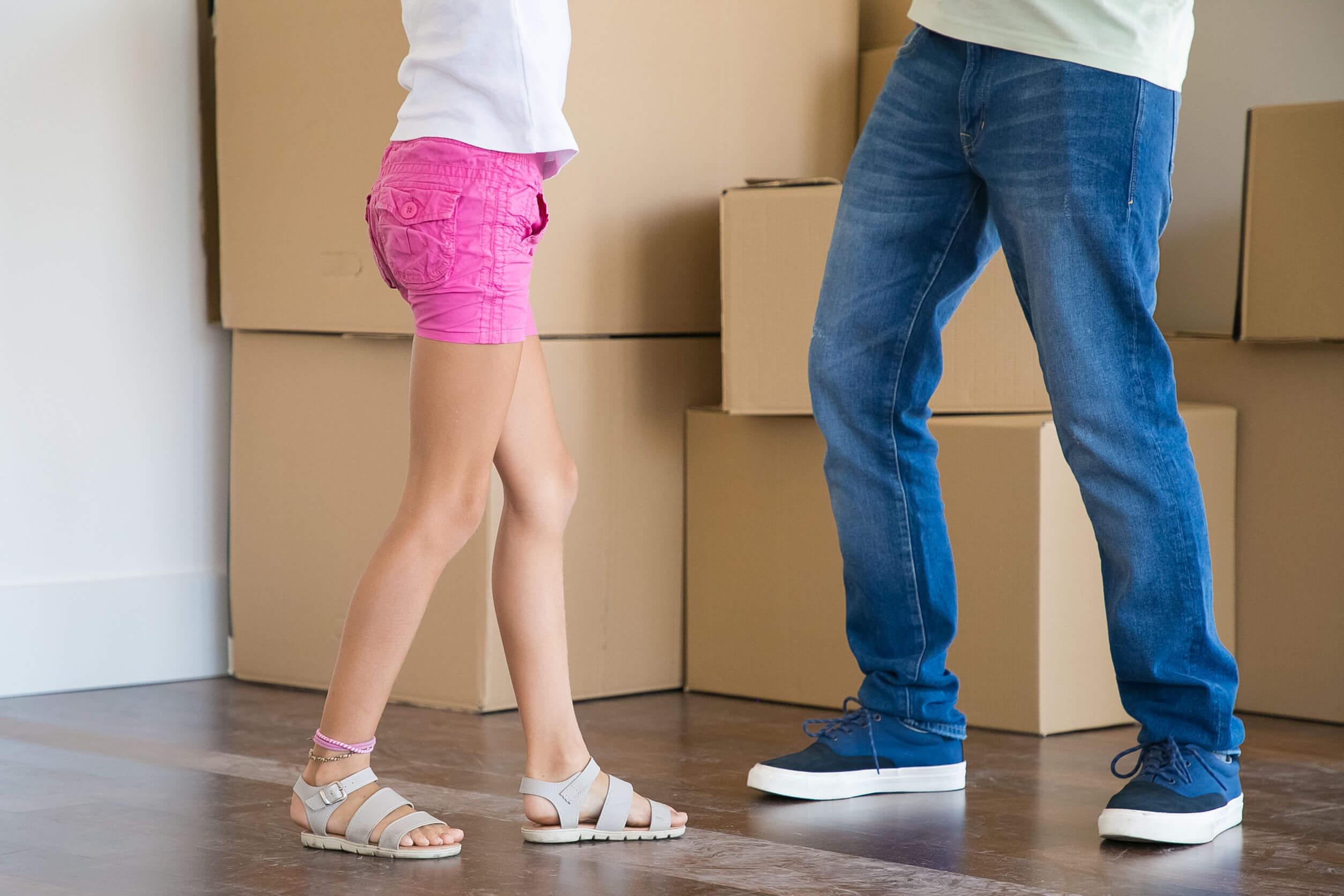 Padre e hija rodeados de cajas de cartón.
