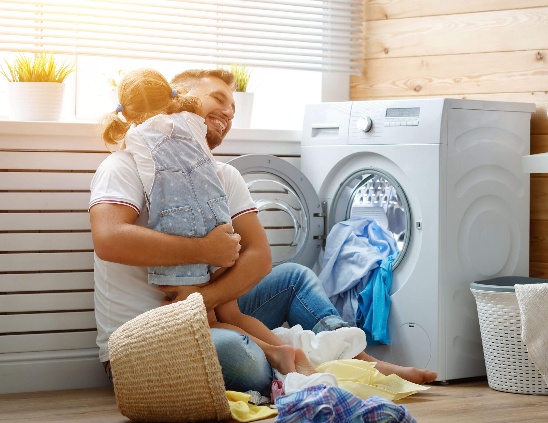 Padre con su hija poniendo una lavadora como parte de las normas de casa.