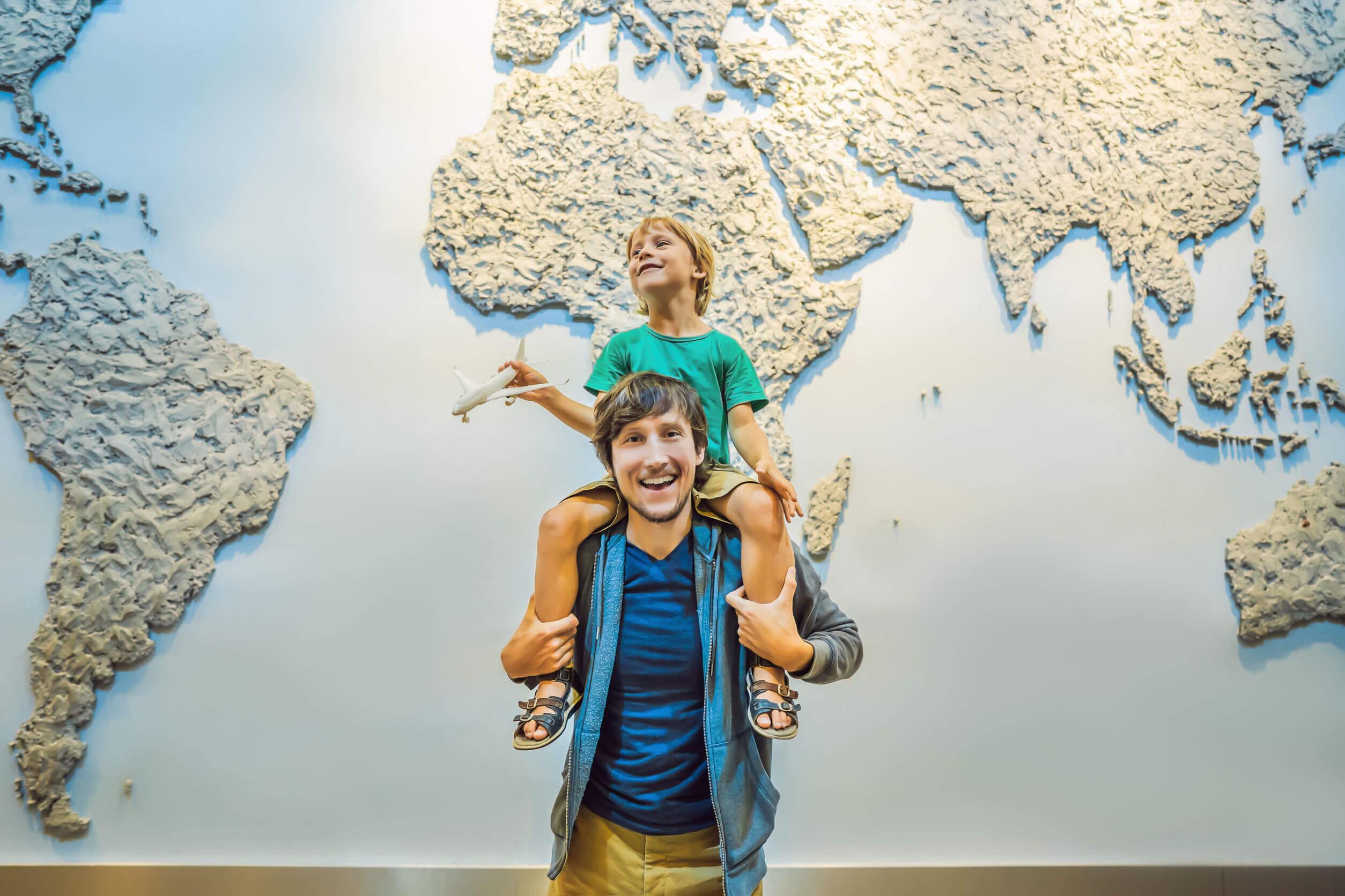 Padre e hijo con un mapamundi detrás.