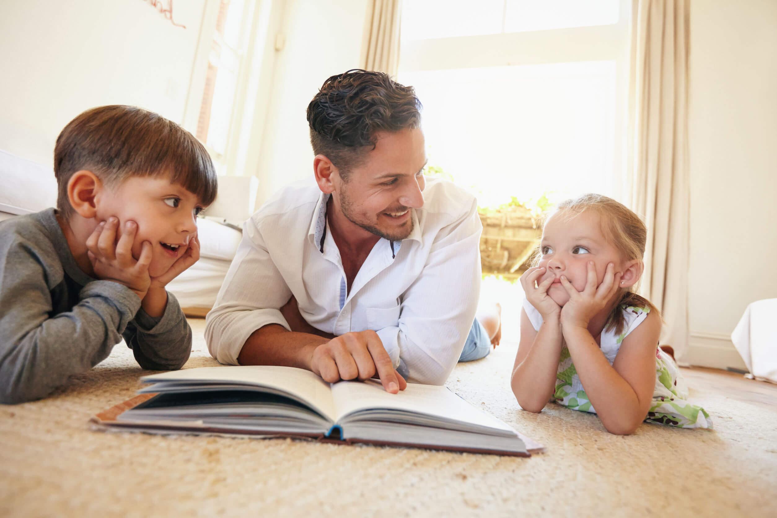 Padre leyendo un cuento a sus hijos para trabajar la gestión de la ira.