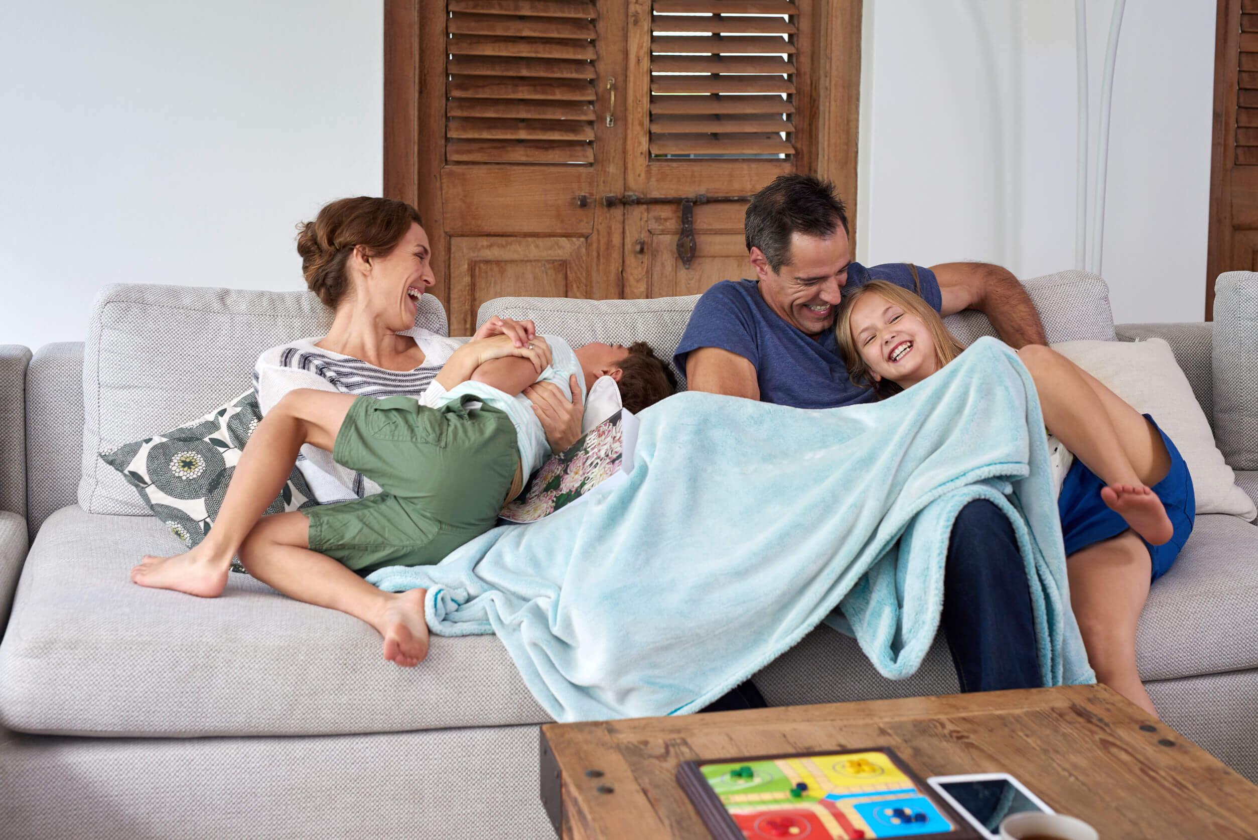 Padres abrazando a sus hijos mientras se ríen en familia.