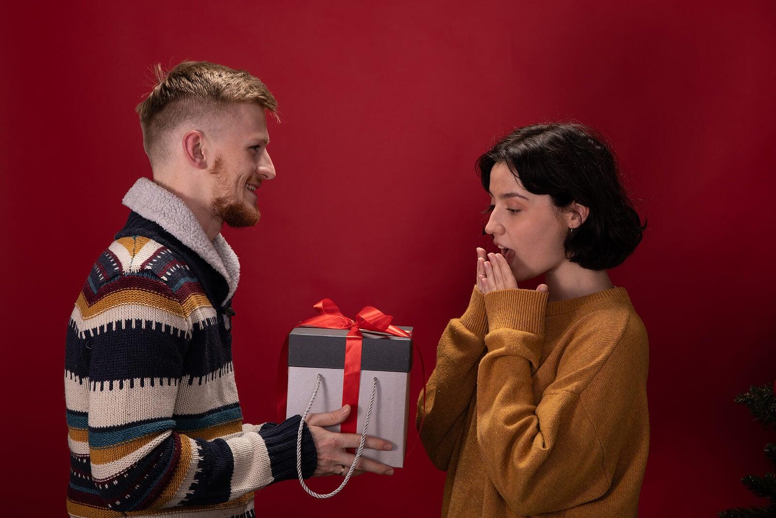 Pareja haciéndose regalos sorpresa.