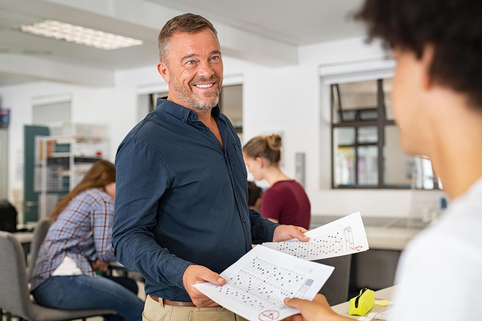 Profesor entregando un examen tipo test corregido a un alumno.