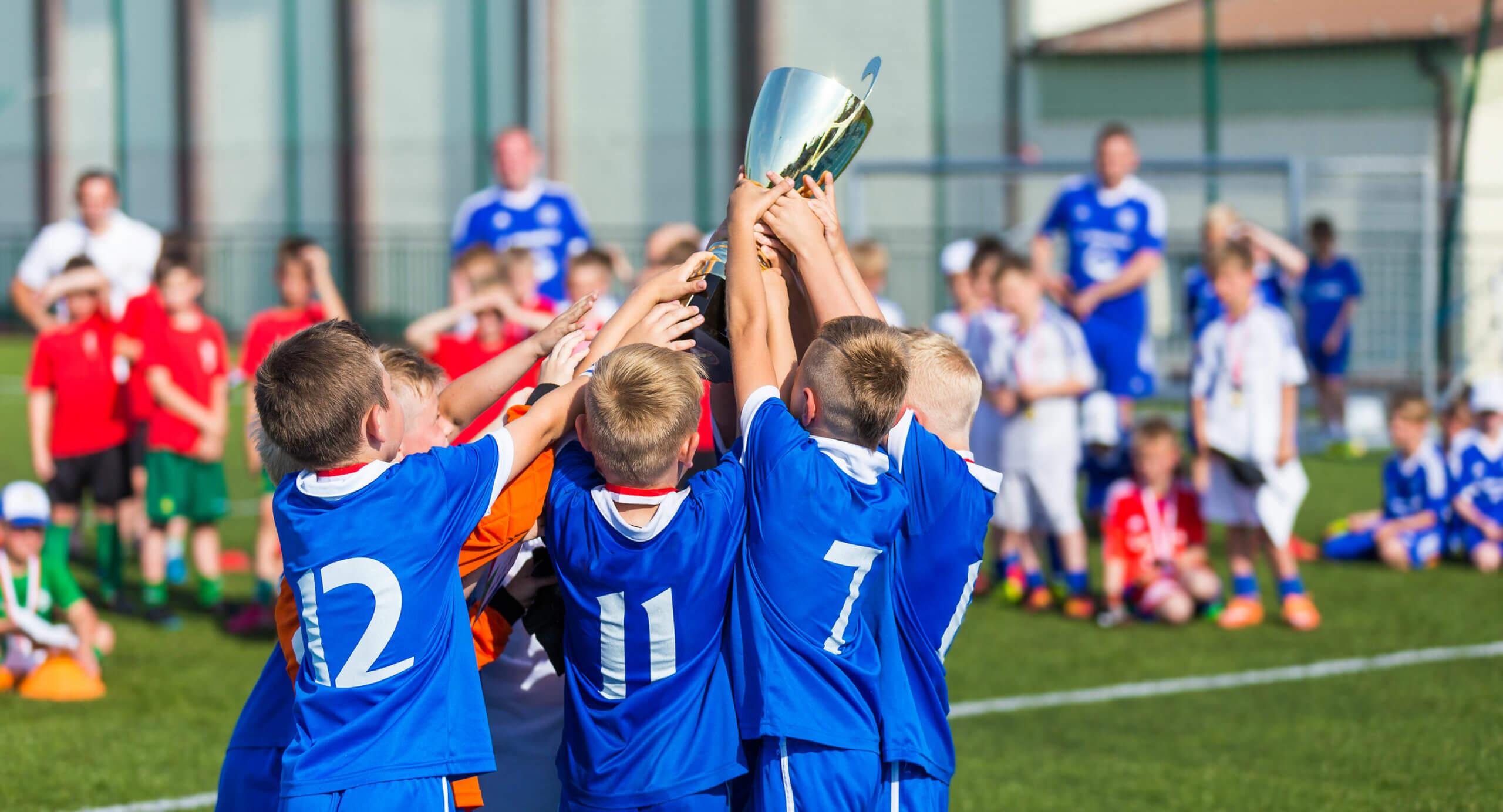 Equipo de fútbol levantando el trofeo tras ganar con deportividad.
