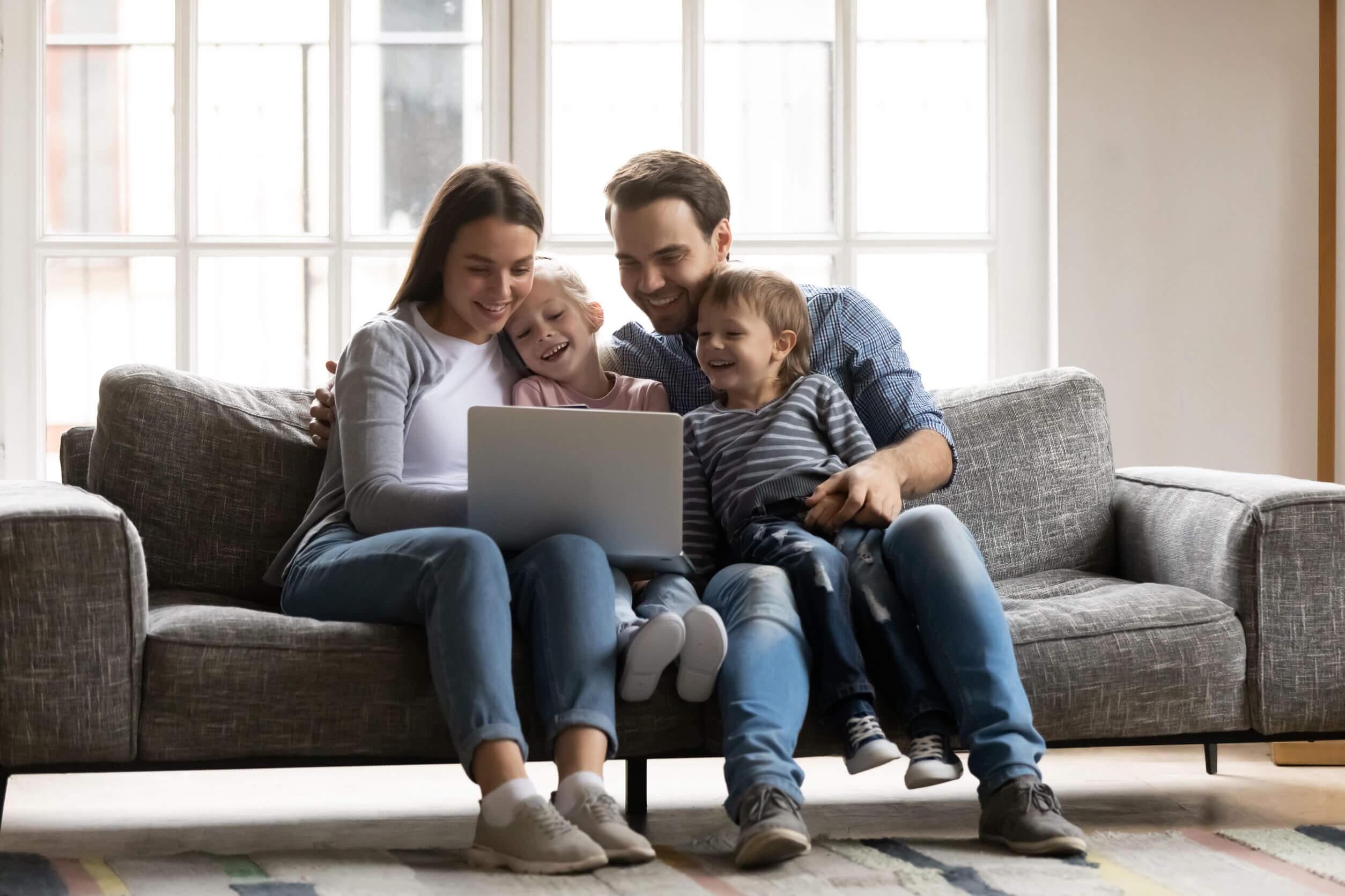 Familia viendo en el ordenador algunos de los mejores canales educativos como parte de los planes gratis online.