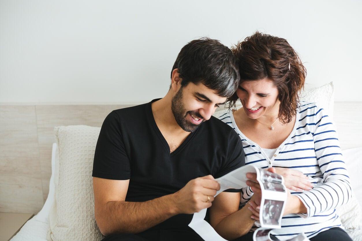 Padres mirando las ecografías y pensando en nombres de niña que empiecen por la letra C.