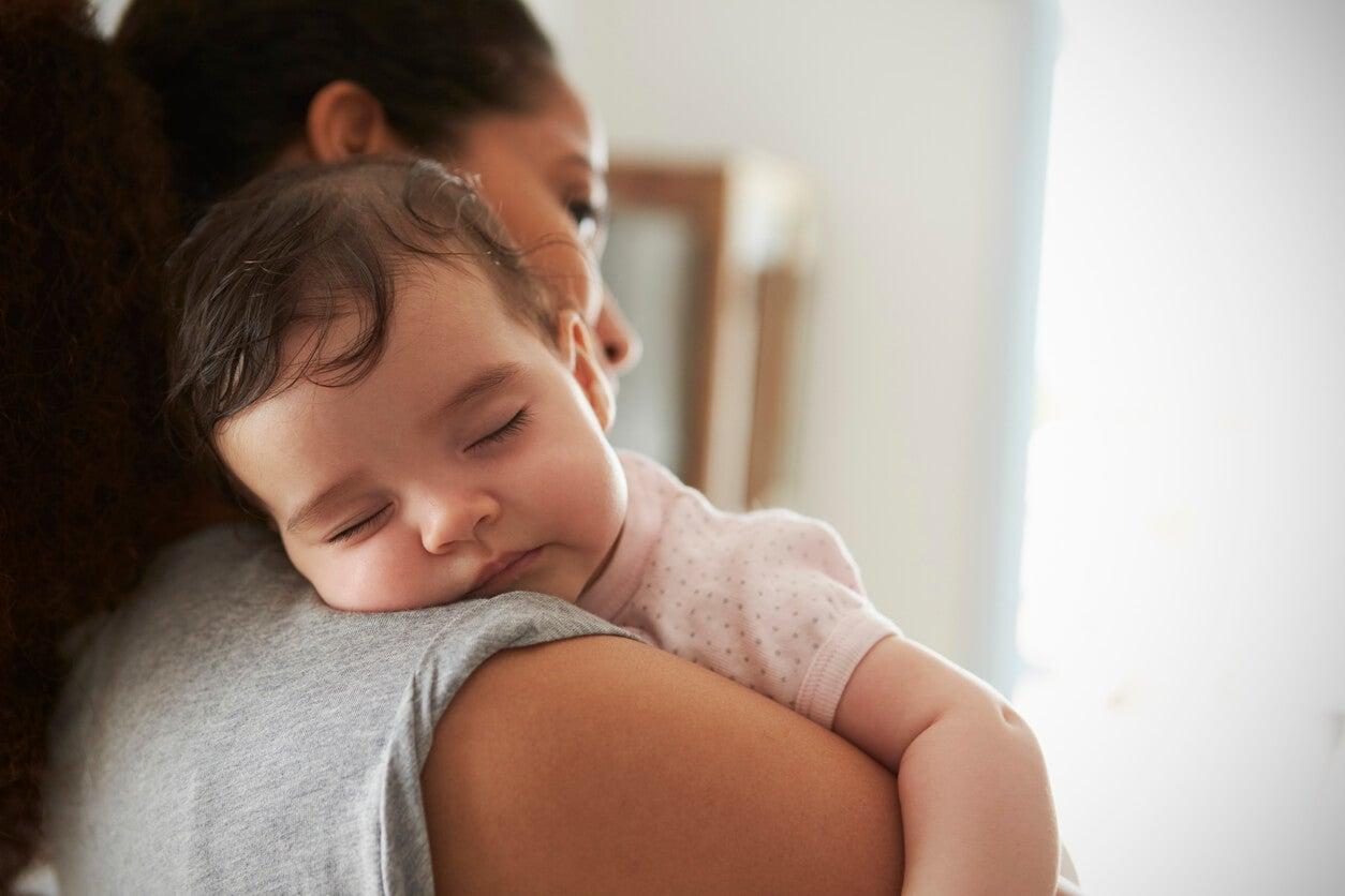 Madre con su hijo en brazos dormido.