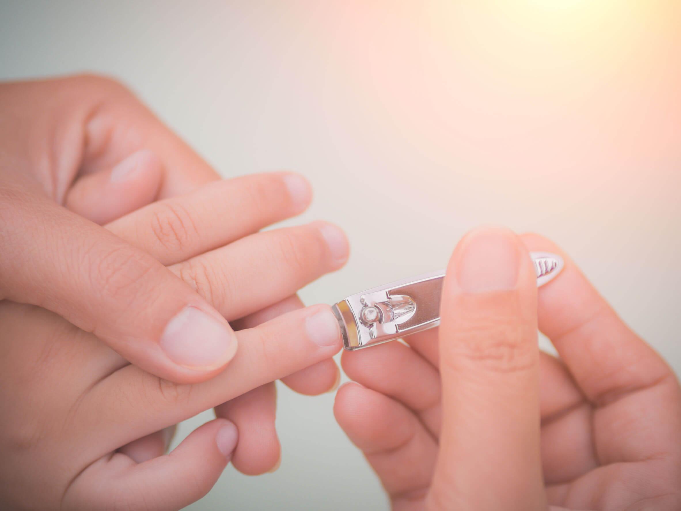 Madre cortándole las uñas a su hijo para evitar los uñeros en bebés y niños.