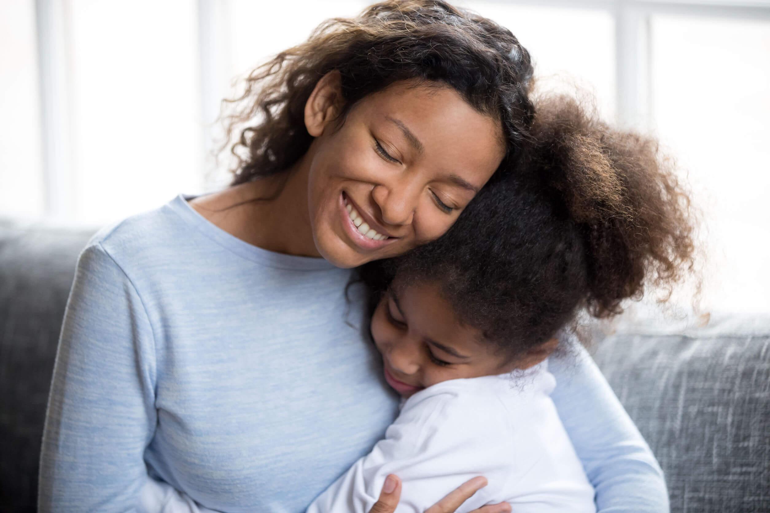 Madre abrazando a su hija mientras le enseña el valor de la amabilidad.