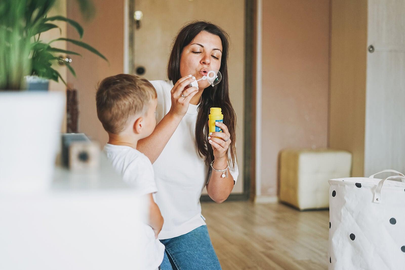Madre e hijo jugando con pompas de jabón.