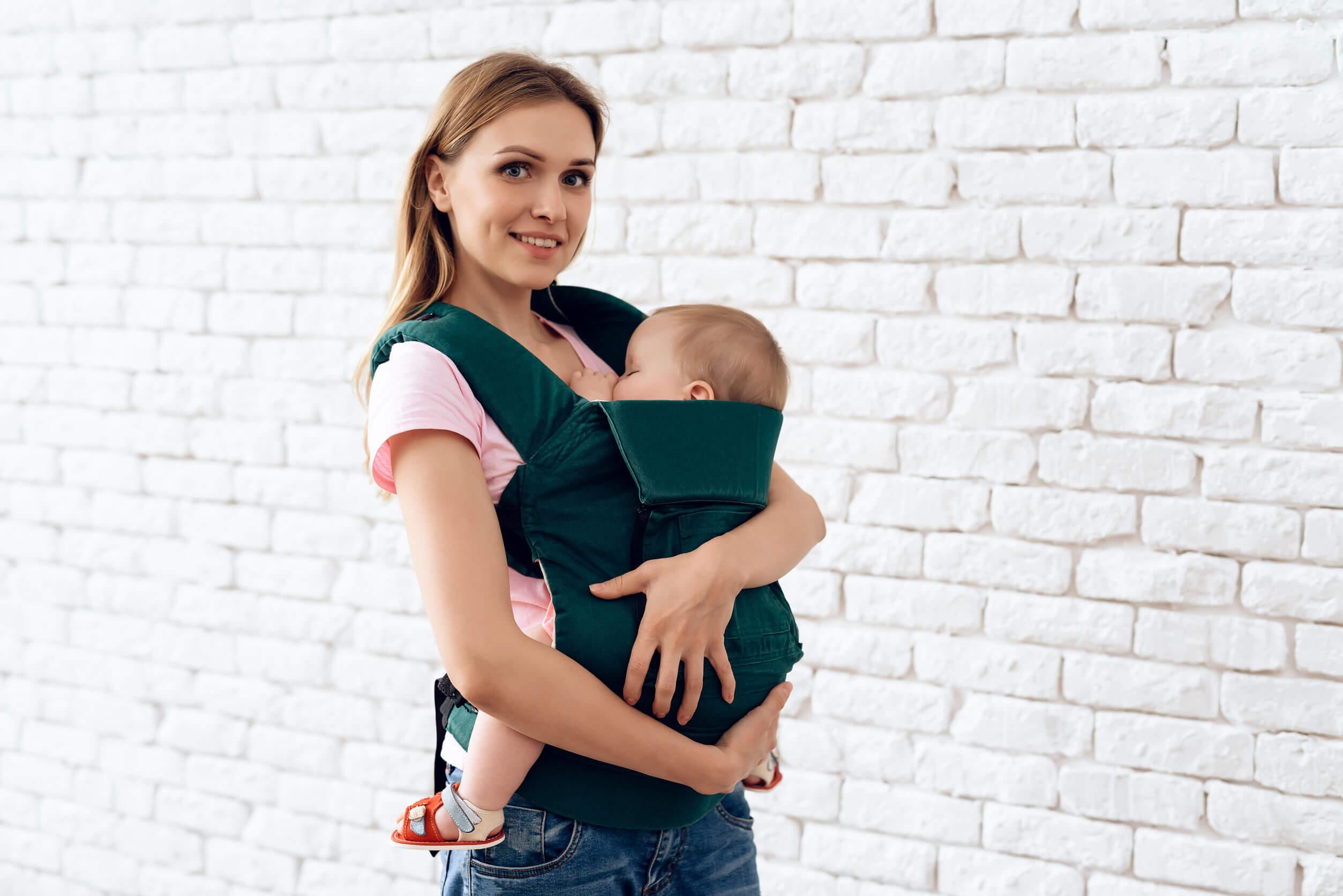 Madre con su hijo probando una mochila postabebés.