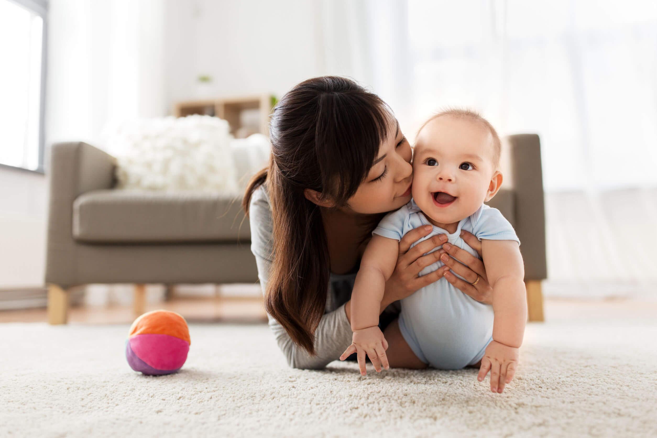 Madre con su bebé explorando el salón de casa.