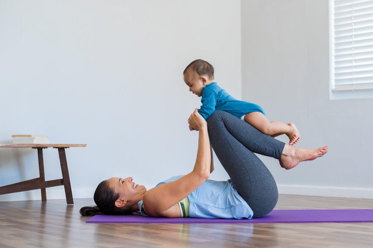 Madre haciendo ejercicio con su bebé después del parto.