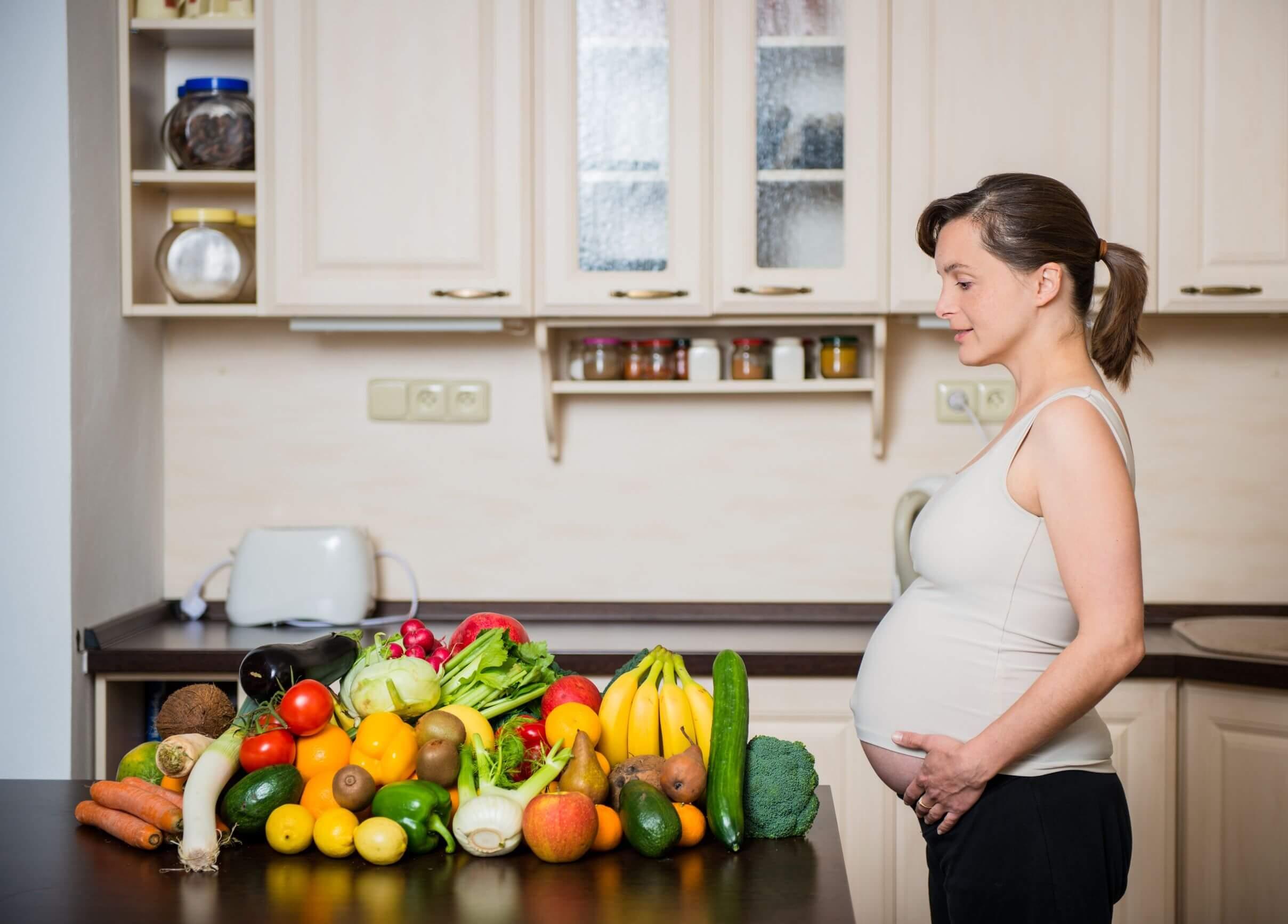 Mujer embarazada tras hacer una compra saludable con verduras de hoja verde.