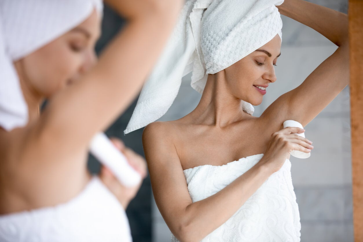 Femme enceinte appliquant un déodorant.